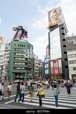 Pedestrians crossing street below billboards advertising fashion products in fashionable Omotesando district in - Stock Photo