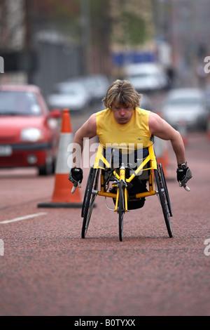wheelchair competitor racing along road during the belfast marathon 2008 belfast city centre northern ireland - Stock Photo