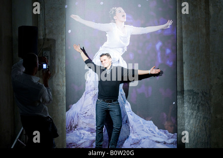 photographer taking a picture a man stading in front of a photo of Bjork - Stock Photo