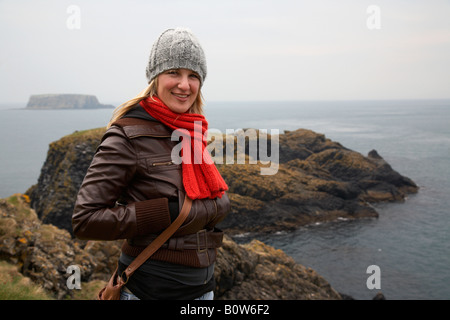cold female tourists standing on carrick a rede island on the the county antrim coast northern ireland on a cold - Stock Photo