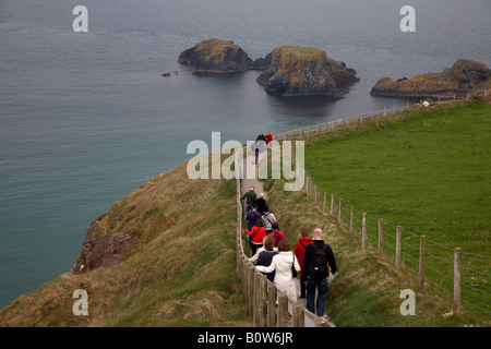 tourists walking down the long pathway to the carrick a rede rope bridge on the county antrim coast northern ireland - Stock Photo