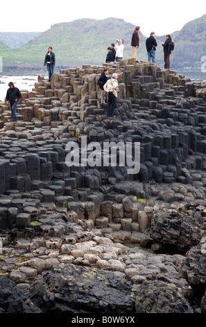 tourists wander round the red basalt hexagonal rock formations at the giants causeway county antrim northern ireland - Stock Photo