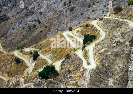 Road winding up arid landscape with sparse vegetation, Castelmola near Taormina, Sicily, Italy, Europe - Stock Photo