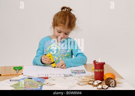 Little girl writing her Christmas wish list for Santa Claus - Stock Photo