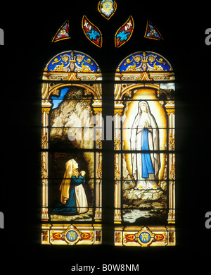 Stained-glass window depicting the Virgin Mary appearing before St. Bernadette, Soubirous, Parish Church of St. - Stock Photo