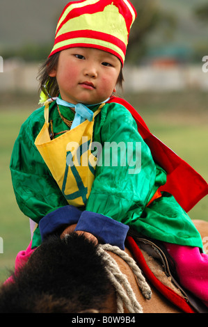 Four-year-old girl riding a horse, participant in the horsemanship competition of the Naadam Festival, Mongolia, - Stock Photo