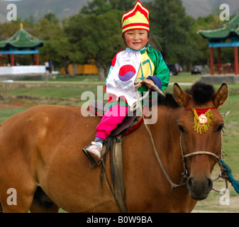 Four-year-old girl riding a horse, participant in the horsemanship competitions of the Naadam Festival, Mongolia, - Stock Photo