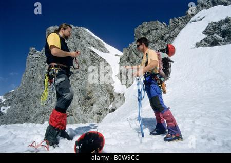 Mountain climbers checking their equipment and preparing a climbing tour, Karwendel, Northern Range, Innsbrucker - Stock Photo