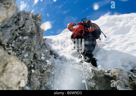Female mountain climber climbing over a cornice on a steel rope, snow sliding and falling down, Northern Range, - Stock Photo