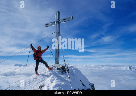 Female mountain climber standing on the summit of Mt. Similaun next to iron summit cross, raising her arms triumphantly - Stock Photo
