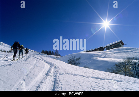 Three ski tourers on a ski tour, ski tour track next to an alpine hut, Tux Alps, Tyrol, Austria, Europe - Stock Photo