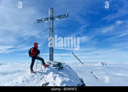 Mountain climber standing on the peak of Mt. Similaun next to an iron summit cross, Tyrol, Austria, Europe - Stock Photo