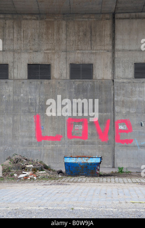 Container in front of a wall with the word love spray-painted in pink - Stock Photo