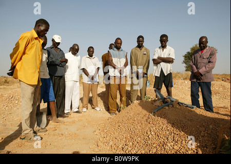 Funeral of a woman who died of HIV/AIDS, men praying at her grave, Garoua, Cameroon, Africa - Stock Photo