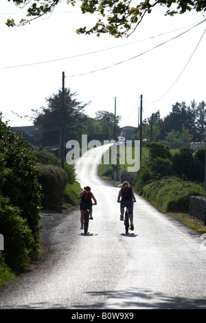 two teenage girls cycling off into the sun along a small narrow country road in county sligo republic of ireland - Stock Photo