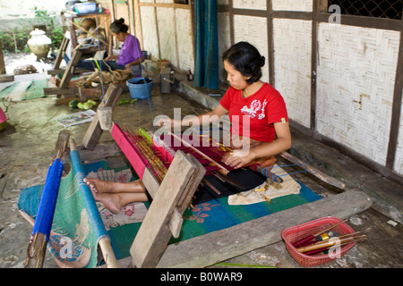 Woman weaving cloth in the traditional method on an old loom, Tete Batu, Lombok Island, Lesser Sunda Islands, Indonesia - Stock Photo
