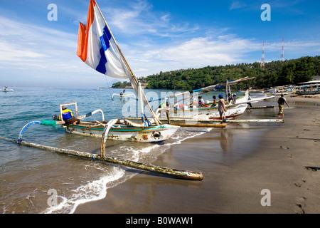 Outrigger fishing boats pulled up onto the beach at Senggigi, Lombok Island, Lesser Sunda Islands, Indonesia - Stock Photo