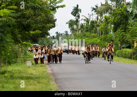 Schoolchildren dressed in uniforms walking along a street after school near Mataram, Lombok Island, Lesser Sunda - Stock Photo