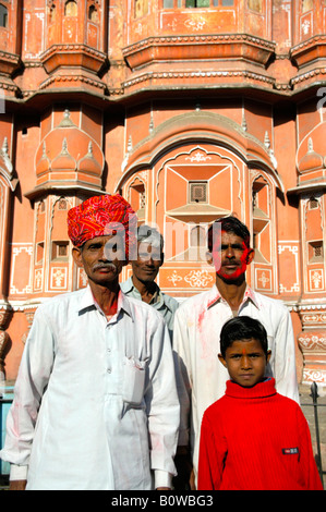 Indian men wearing turbans and red colour on their face standing in front of the Hawa Mahal or Palace of Winds in - Stock Photo
