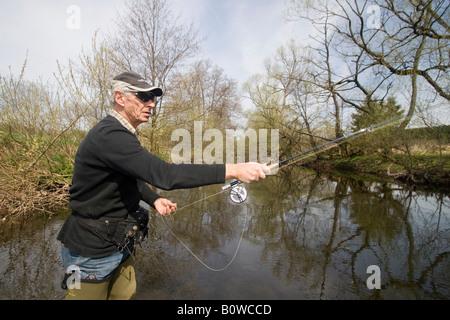Fly fisherman casting a fishing rod, Vulkaneifel, Rhineland-Palatinate, Germany, Europe - Stock Photo