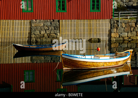 Red painted wooden house and rowboats reflected in the water, Stamsund, Vestvagoey, Lofoten, Norway, Scandinavia - Stock Photo