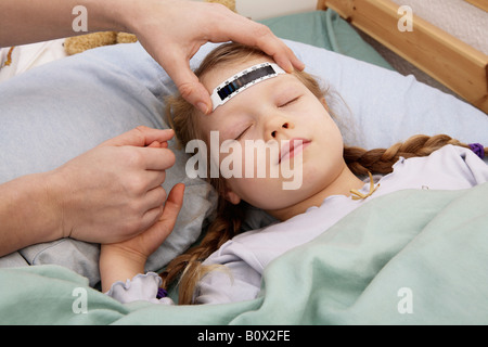 A young girl having her temperature taken with a forehead thermometer strip - Stock Photo