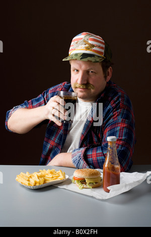 Stereotypical American man with burger, fries and a cola - Stock Photo