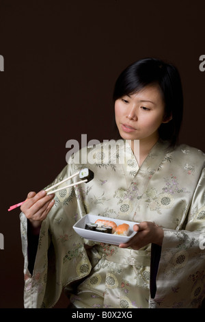 A woman dressed in a kimono eating sushi - Stock Photo