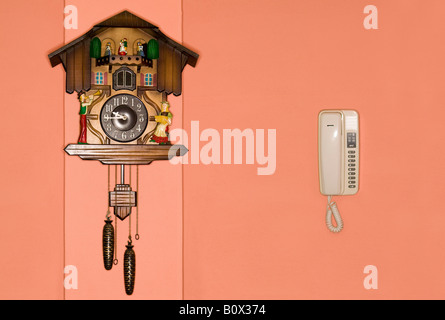 A cuckoo clock and a telephone on a wall - Stock Photo