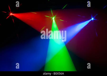Three multi colored spotlights crossing light beams - Stock Photo
