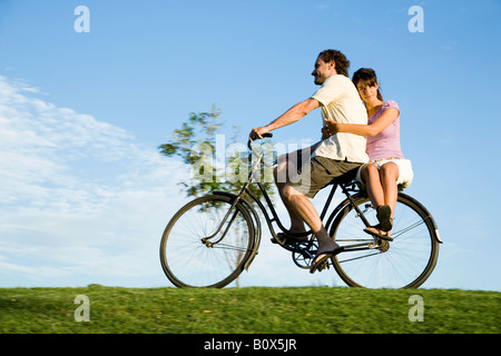 A man riding a bicycle and a young woman sitting on the back - Stock Photo