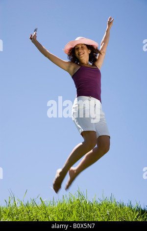 A young woman leaping in the air and holding a mobile phone - Stock Photo