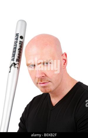 bald headed man with baseball bat looking roguish into the camera - Stock Photo