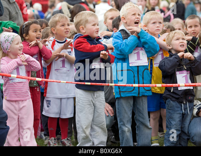 Children up to 6 years of age on start line with start numbers on warming up to run a race - Stock Photo