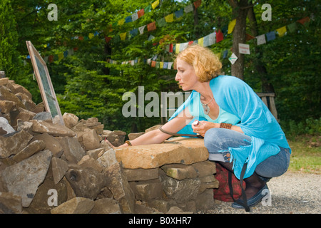A woman offering incense on a small stone altar near a tibetan buddhist stupa situated in Hungary, close to Lake - Stock Photo