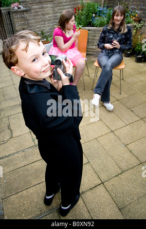 young boy in suit using video camera (camcorder) - Stock Photo
