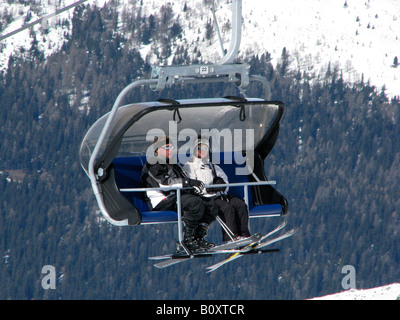Skiers sitting in a chair ski lift in snowy mountain scenery, Italy, Suedtirol - Stock Photo