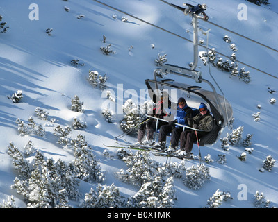 Skiers sitting in a chair ski lift in snowy mountain scenery of a skiing area, Italy, Suedtirol, Reinswald, Sarntal - Stock Photo
