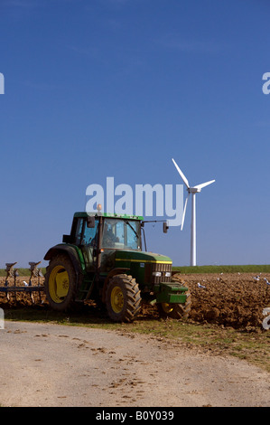 A tractor ploughing a field, with a wind turbine in the background - Stock Photo