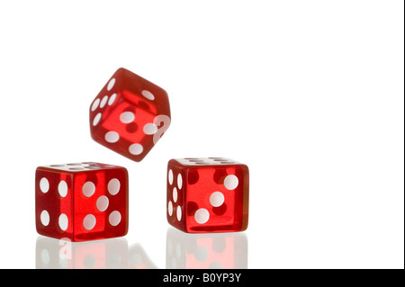Three red dice being rolled on a white background these are the type of dice used in casinos around the world - Stock Photo