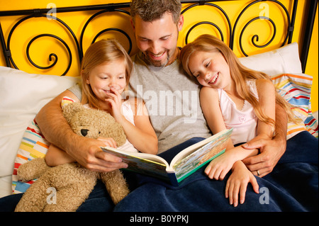 A father reading to his children in bed. - Stock Photo