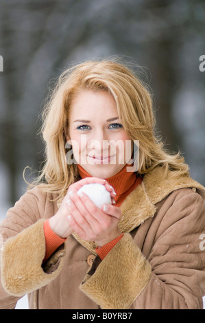 Austria, Salzburger Land, Altenmarkt, Young woman holding a snowball, smiling, portrait - Stock Photo
