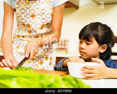 Daughter watching mother preparing food, cropped - Stock Photo