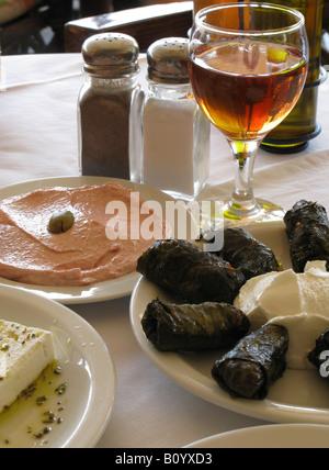 Greek Cuisine Taramasalata Dolmades Feta cheese and glass of red wine Chania Crete Greece - Stock Photo