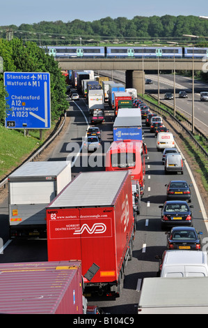 M25 motorway nose to tail slow moving traffic fast train on bridge - Stock Photo