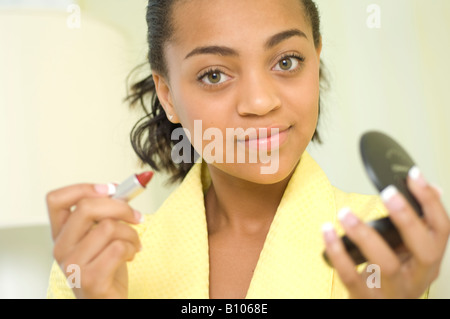 spanish african teenage girl doing her make up - Stock Photo
