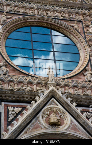 Closeup facade of the Duomo of Siena, detail view with Clouds reflected in rose glass window behind Giovanni Pisano - Stock Photo