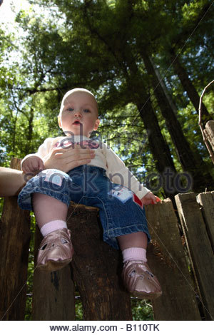 A baby being held up on a fence. - Stock Photo
