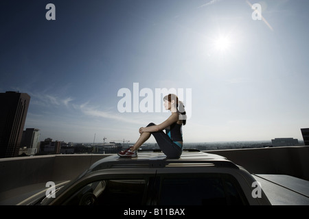 Woman Sitting On Top Of Suv Drinking Water On Roof Top Car Park