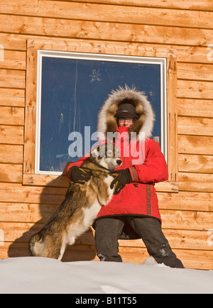 Dogsled musher Julie Estey with one of her racing dogs by her cabin in Fairbanks - Stock Photo